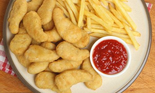 A plate of chicken dippers with some ketchup and fries.