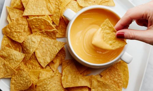 A plate of tortilla chips and cheese dip.