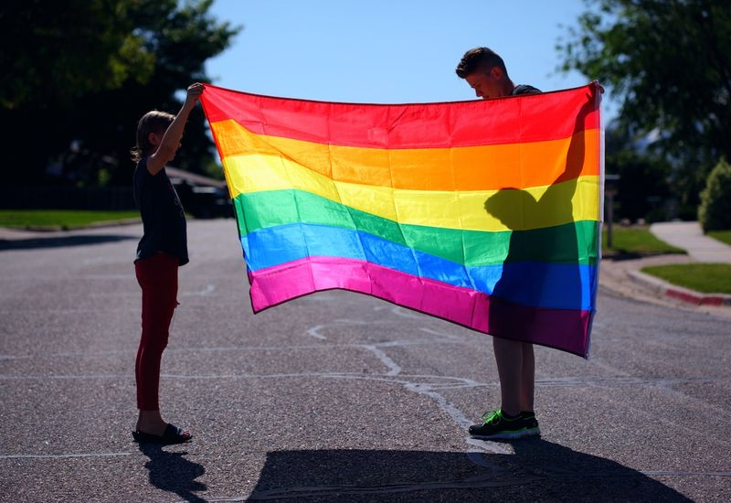 Man and child holding rainbow flag.